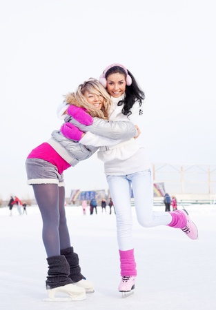 two beautiful girls ice skating outdoor on a warm winter day photo