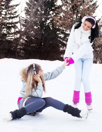 winter day: two beautiful girls ice skating outdoor on a warm winter day