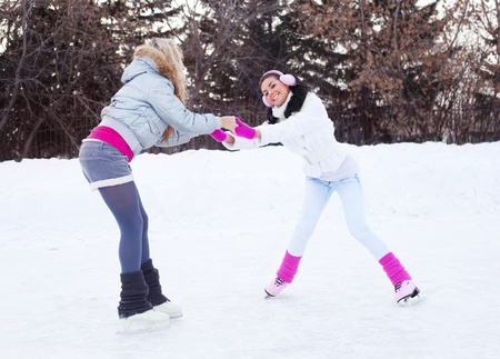 two beautiful girls learning ice skating outdoor on a warm winter day Stock Photo - 11151414
