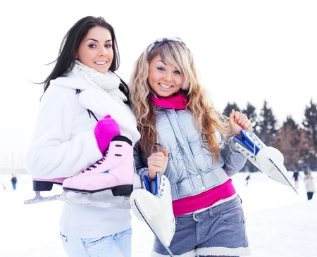 skate park: two beautiful girls wearing warm winter clothes going  ice skating Stock Photo