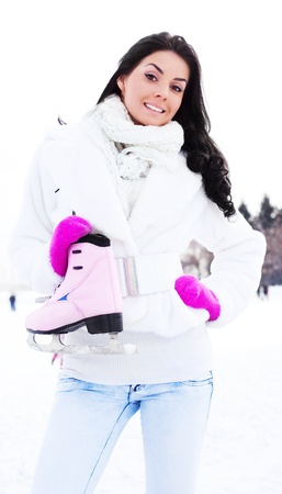 wintertime: happy beautiful girl wearing warm winter clothes going to ice skate