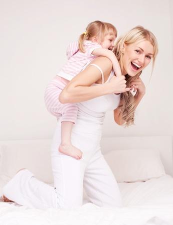 háton: boldog fiatal anya játszik lányával az ágyon otthon Stock fotó
