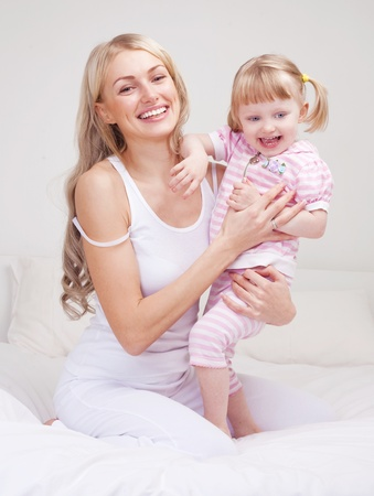 happy young mother playing with her daughter on the bed at home (focus on the woman) photo