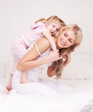 piggyback ride: happy young mother playing with her daughter on the bed at home Stock Photo