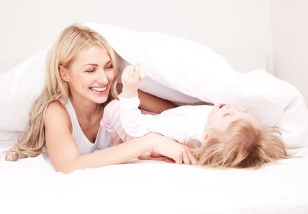 mujer en la cama: joven madre feliz jugando con su hija bajo la s�bana de la cama en su casa (se centran en la mujer) Foto de archivo