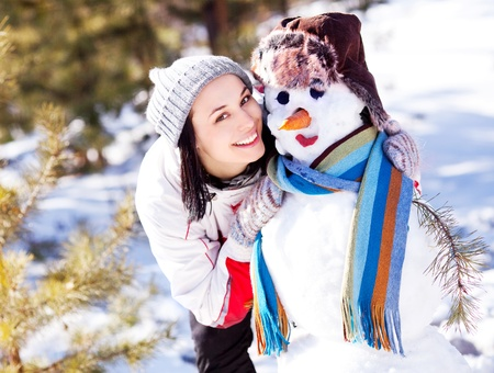 portrait of a pretty young brunette woman with a snowman outdoor on a warm winter day