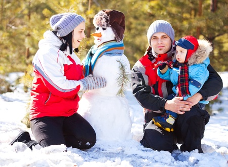 happy family: mother, father and son making a snowman outdoor on a warm winter day (focus on the woman) Stock Photo