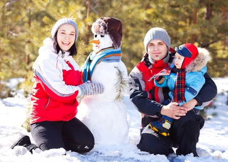 happy family: mother, father and son making a snowman outdoor on a warm winter day (focus on the woman) photo