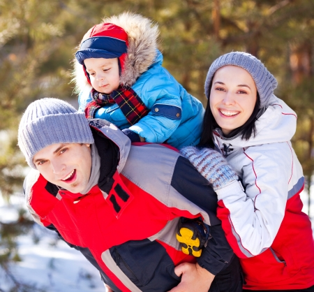 outsides: happy family: mother, father and son  spending time outdoor on a warm winter day (focus on the  woman)