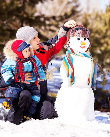 outsides: father and son making a snowman outdoor on a warm winter day