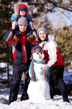 winter day: happy family: mother, father and son making a snowman outdoor on a warm winter day (focus on the woman) Stock Photo