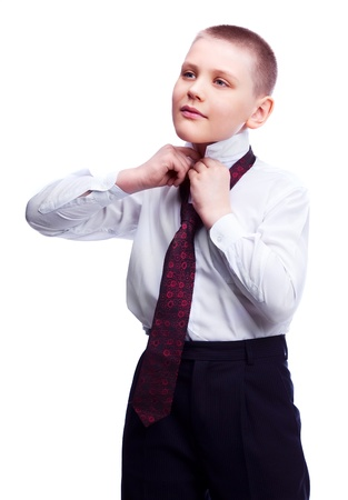 confident ten year old blond boy putting on a  tie , isolated against white photo