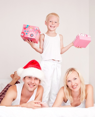 happy family celebrating Chritmas and opening presents: mother ,father and their son on the bed at home   photo