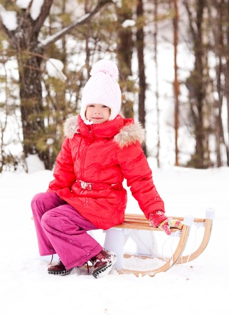 outsides: happy little girl on the sledge outdoor on a winter day