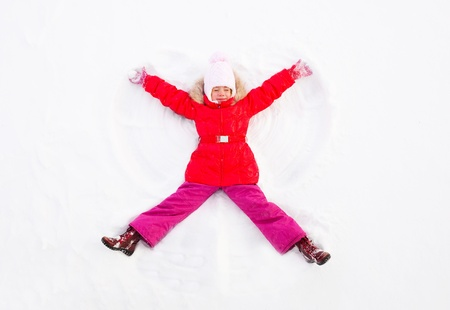 making fun: Girl Laying On the Ground Making Snow Angel Stock Photo