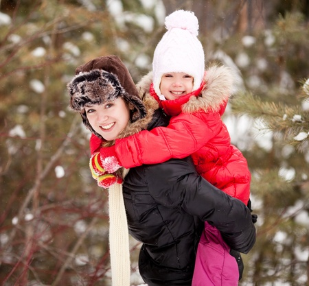 piggyback ride: happy  family; mother and daughter  outdoor on a warm winter day Stock Photo