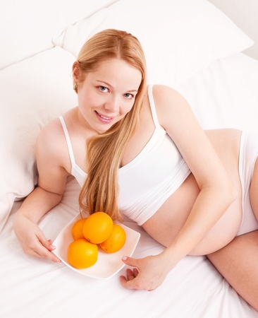 beautiful young pregnant woman  with oranges in bed at home smiling photo