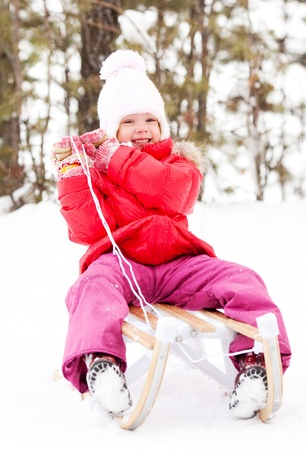 happy little girl on the sledge outdoor on a winter day photo