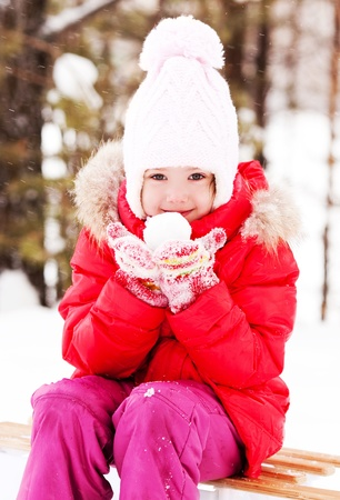 happy little girl on the sledge with a snowball in her hands outdoor on a winter day photo