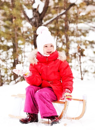 happy little girl sitting on the sledge and throwing a snowball,  outdoor in the park on a winter day photo
