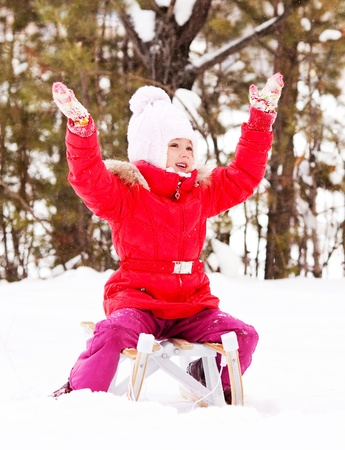 happy little girl sitting on the sledge outdoor on a winter day photo