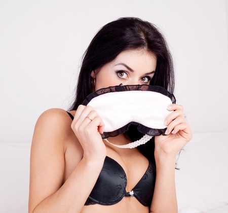 sexy young brunette woman with a sleep mask on the bed at home Stock Photo - 11306395