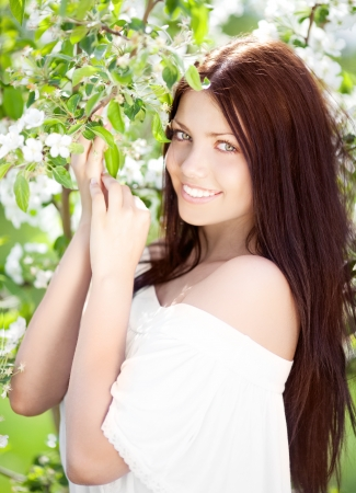 natural hair: beautiful young brunette woman with the apple tree on a warm summer day Stock Photo