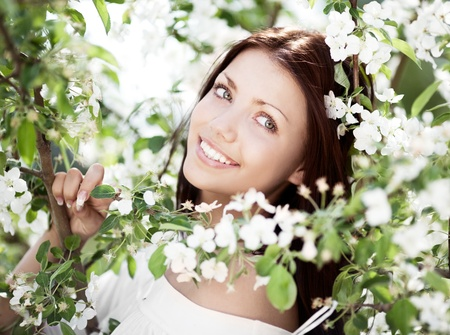 outsides: beautiful young brunette woman with the apple tree on a warm summer day Stock Photo