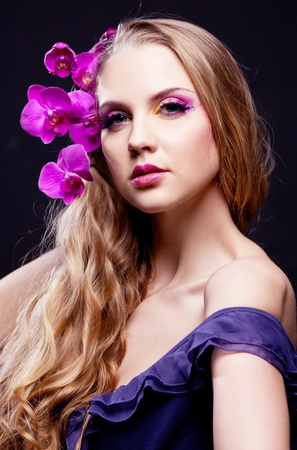 long silky hair: beautiful young woman with long curly hair and an orchid, isolated against black studio background