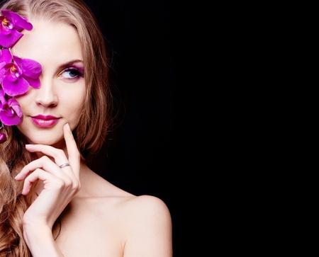 modellini: bella giovane donna con lunghi capelli ricci e un'orchidea, isolato su sfondo nero in studio, copia-spazio per il testo a destra