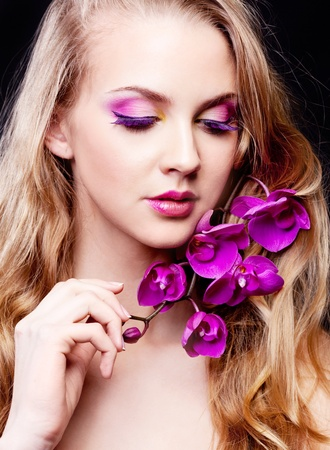 purple dress: beautiful young woman with long curly hair and an orchid, isolated against black studio background