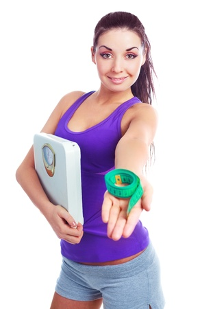 woman measuring: beautiful young woman wearing sports clothes holding scales and a measuring tape, isolated against white background   Stock Photo