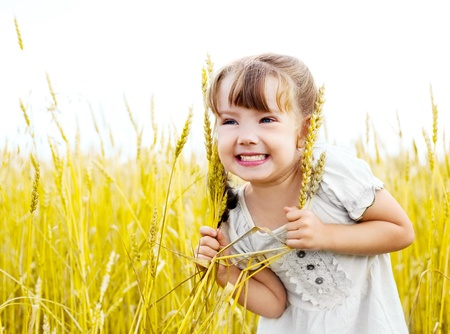 outsides: happy cute girl in the wheat field on a warm summer day