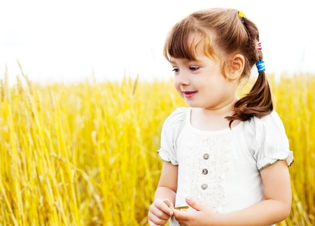 happy cute girl in the wheat field on a warm summer day photo