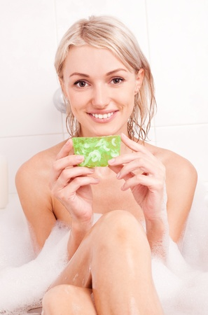 beautiful young blond woman taking a bath with foam and using a  glycerin soap photo