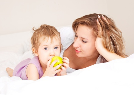 young beautiful mother and her baby on the bed at home photo