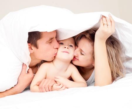 vater und baby: gl�ckliche Familie, Mutter, Vater und ihr Baby unter der Bettdecke auf dem Bett zu Hause (Fokus auf die Frau) Lizenzfreie Bilder