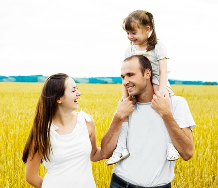 shoulder ride: happy family; mother, father and child at the wheat field on a sunny day