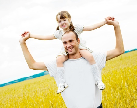 shoulder ride: happy family;  father and his daughter at the wheat field on a sunny day (focus on the  man) Stock Photo