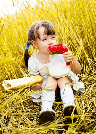 happy cute little girl having a picnic in the wheat field drinking milk and eating a long loaf