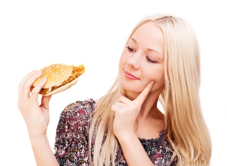thoughtful young woman eating a hamburger with chicken, isolated against white background photo