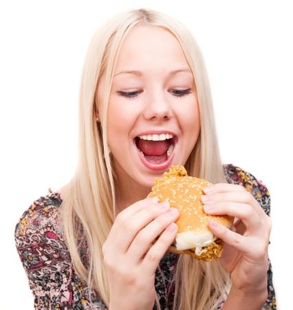 niña comiendo: mujer joven feliz comiendo una hamburguesa de pollo, aislado contra el fondo blanco Foto de archivo