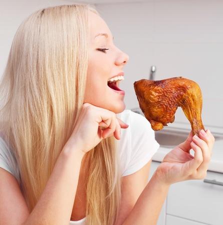 carne de pollo: joven y bella mujer rubia de comer pollo en la cocina de su casa