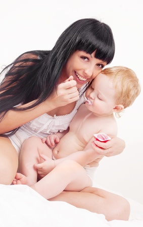 happy young mother feeding her baby with yogurt  at home photo