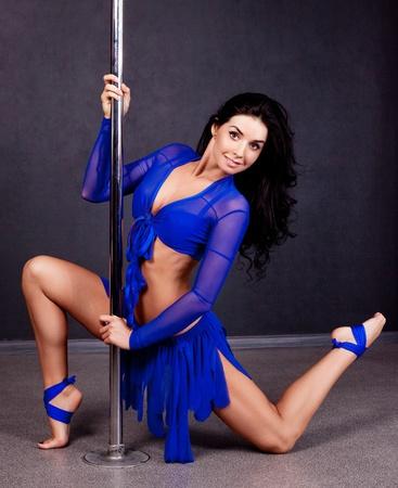 pole dance: ritratto di una giovane donna sexy pole dance sul pavimento