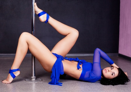 metal pole: portrait of a young sexy pole dance woman on the floor