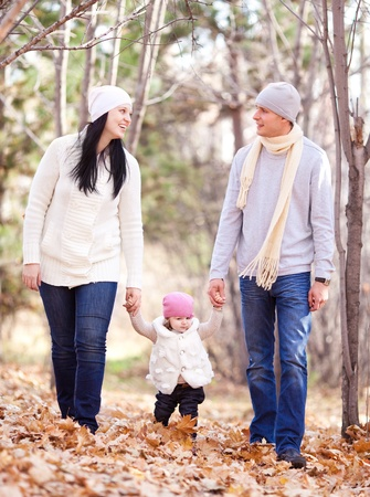 happy young family with their daughter spending time outdoor in the autumn park Stock Photo - 11557228