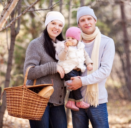 happy young family with their daughter having a picnic in the autumn park   photo