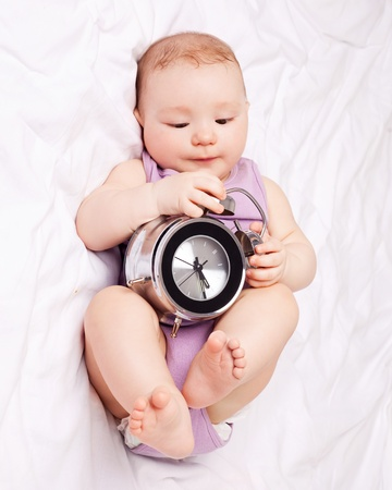 six months: cute six months old baby in  bed at home with an alarm clock Stock Photo