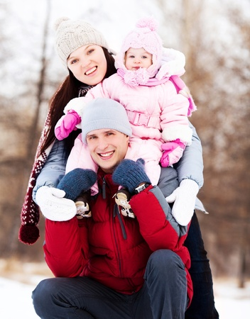 happy young father, mother and their daughter spending time outdoor in the winter park (focus on the man) photo